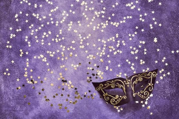 Schwarze karnevalsmaske und goldene sterne auf ultraviolett. draufsicht, kopierraum.