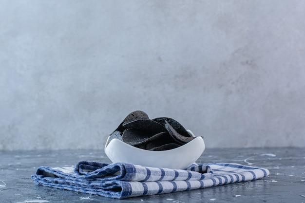 Schwarze kartoffelchips in schüssel auf geschirrtuch, auf der marmoroberfläche