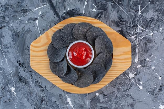Schwarze kartoffelchips und ketchup in holzplatte, auf der marmoroberfläche