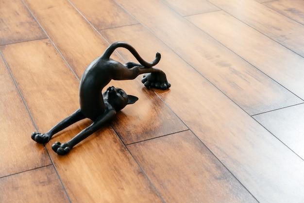 Schwarze katze aus keramik, die sich beim yoga-pose bückt
