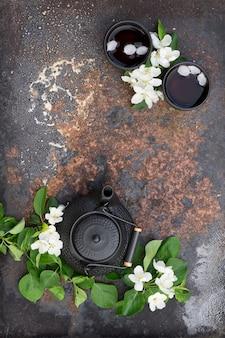Schwarze keramik-teekanne und tasse mit heißem tee, verziert durch apfelzweige der frühlingsblüte über rustikalem eisen mit dunkler textur