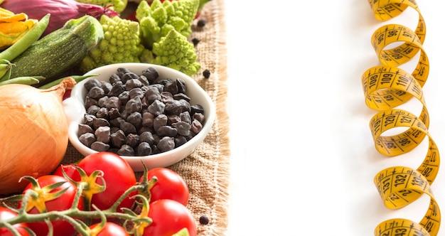Schwarze kichererbse und rohes gemüse mit maßband lokalisiert auf weißer nahaufnahme