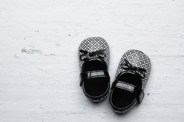 Schwarze kinderschuhe auf weißem hölzernem hintergrund des schmutzes