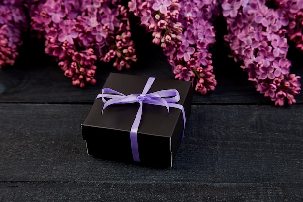 Schwarze kleine geschenkbox mit lila schleife mit natürlichem flieder umwickelt