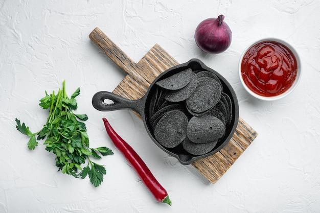 Schwarze, knusprige kartoffelchips mit dip-saucen, tomatendip-sauerrahm, in gusseiserner pfanne, auf weißer steinoberfläche, draufsicht flach