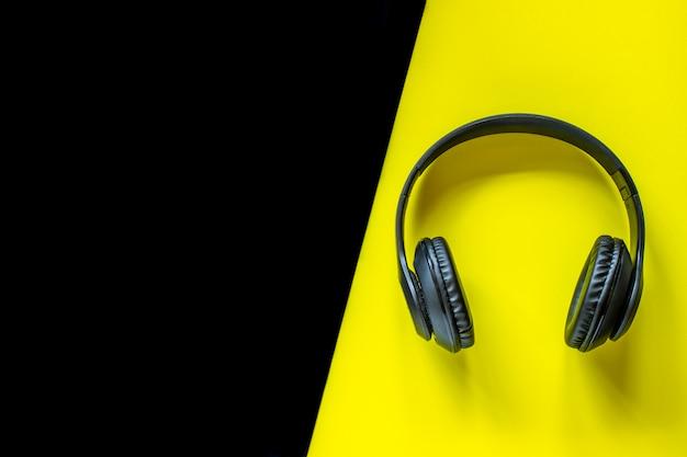 Schwarze kopfhörer auf einem gelb. minimal. flach liegen.