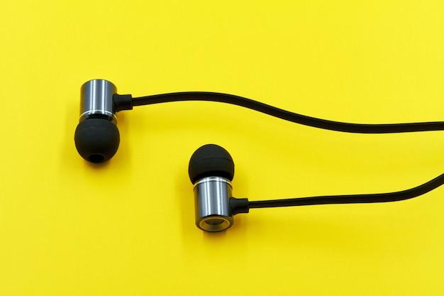 Schwarze kopfhörer auf einem gelben tisch