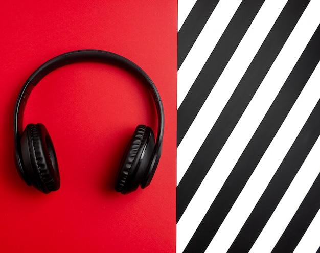 Schwarze kopfhörer auf einem roten hintergrund. minimales konzept. flach liegen.
