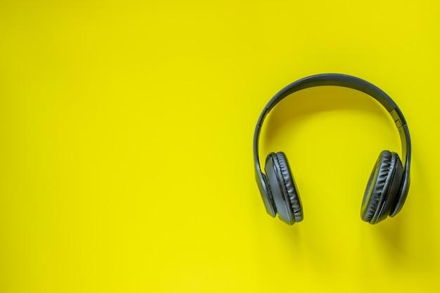 Schwarze kopfhörer auf gelbem grund. minimales konzept. flach liegen.