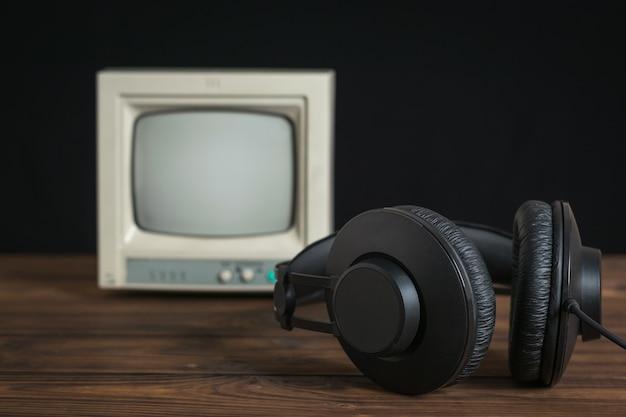 Schwarze kopfhörer mit einem draht auf dem hintergrund eines kleinen monitors für die videoüberwachung. technik zur ton- und videowiedergabe.