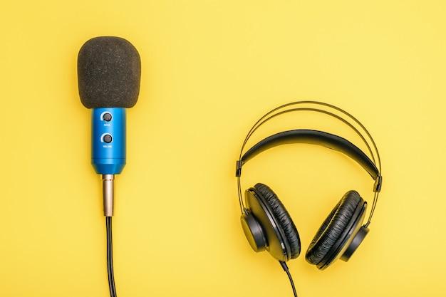 Schwarze kopfhörer und blaues mikrofon auf hellgelbem.