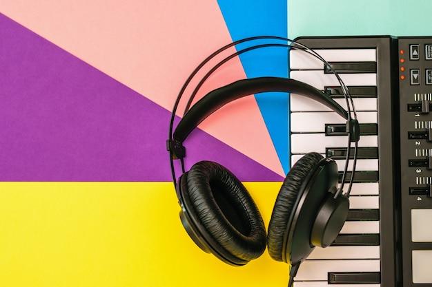 Schwarze kopfhörer und ein musikmixer auf einem mehrfarbigen hintergrund. ausrüstung zum aufnehmen von musiktiteln. der blick von oben. flach liegen.