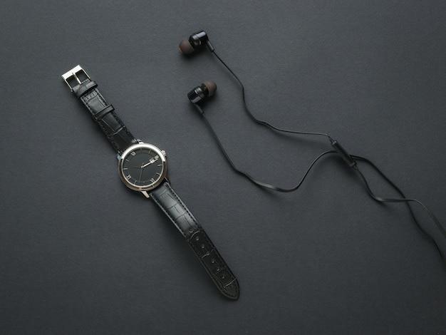 Schwarze kopfhörer und eine schwarze herrenuhr auf schwarzem hintergrund. modeaccessoires für herren.