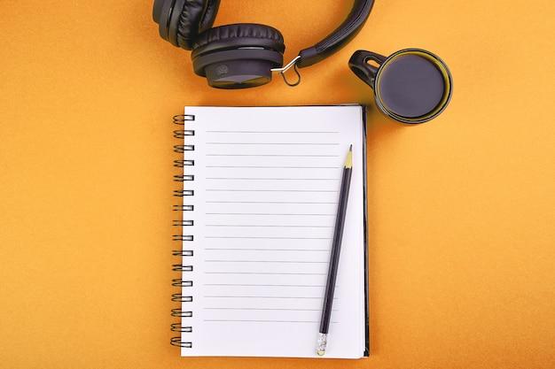 Schwarze kopfhörer und tasse kaffee mit notizbuch