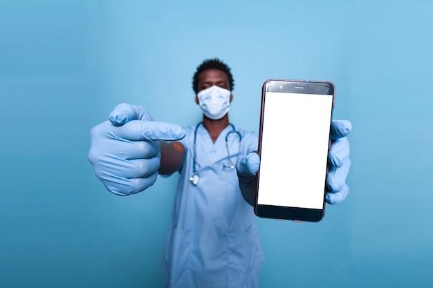 Schwarze krankenschwester, die auf einen leeren weißen bildschirm auf dem smartphone zeigt