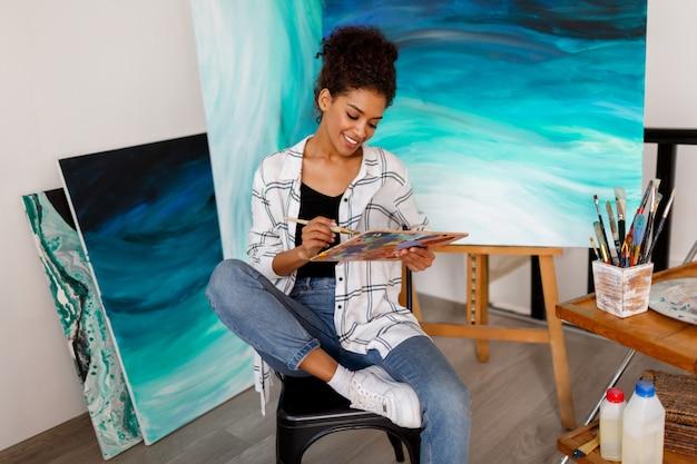 Schwarze künstlerin im studio, die einen pinsel hält. inspirierte studentin, die über ihren kunstwerken sitzt.