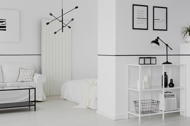 Schwarze lampe auf einem regal an der wand mit postern im weißen open-space-interieur mit sofa und bett