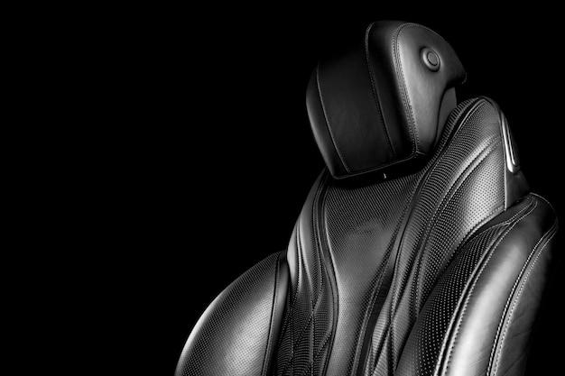 Schwarze lederausstattung des modernen luxusautos. bequeme sitze aus perforiertem leder mit nähten auf schwarzem hintergrund. details der modernen fahrzeuginnenausstattung.