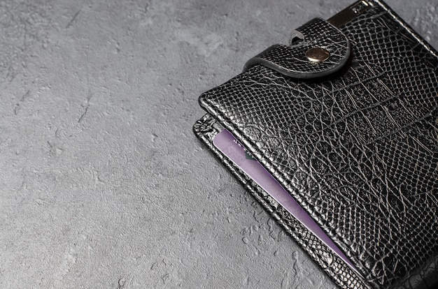 Schwarze lederbrieftasche auf dunklem betonhintergrund