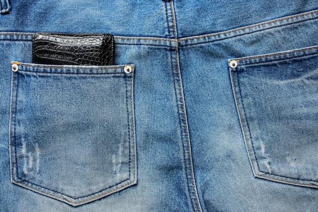 Schwarze lederbrieftasche in der hinteren jeans-hintergrundtextur der blauen jeans.