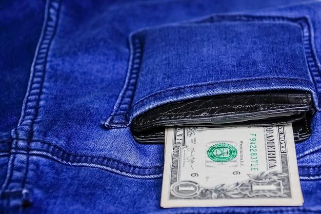 Schwarze lederbrieftasche mit geld in der hinteren jeans-hintergrundtextur der blauen jeans.