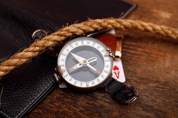 Schwarze lederne geldbörse mit alter spielkarte und seil mit kompass