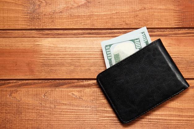 Schwarze lederne geldbörse mit geld auf hölzernem hintergrund. draufsicht