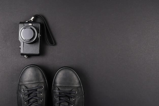 Schwarze lederschuhe der männer und eine schwarze kamera auf einem schwarzen hintergrund. speicherplatz kopieren.