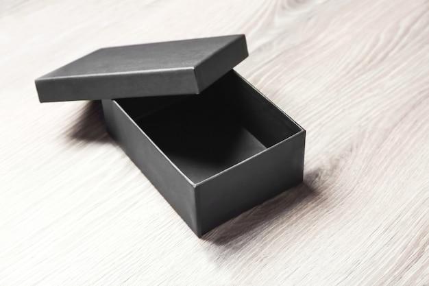 Schwarze leere kiste auf holzoberfläche