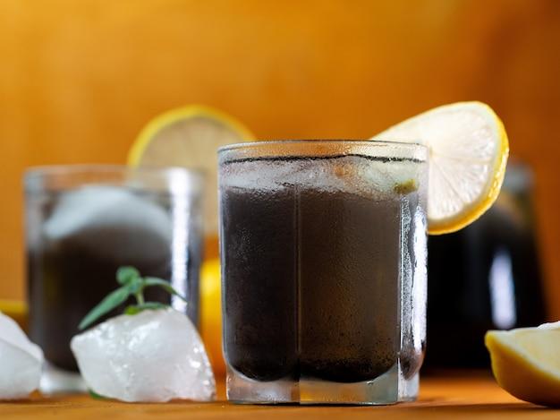 Schwarze limonade mit minze, zitrone, holzkohle und eis auf einem holztisch