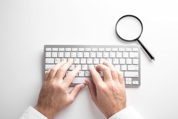 Schwarze lupe auf einer weißen tastatur auf einem weißen hintergrund. geschäftskonzept.