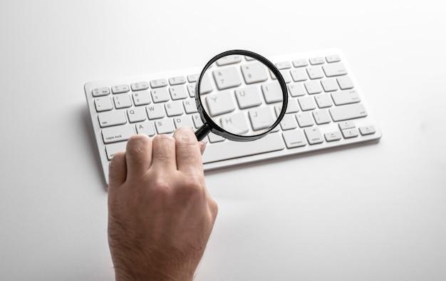 Schwarze lupe auf einer weißen tastatur auf einem weißen tisch. geschäftskonzept.