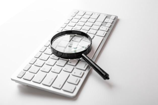Schwarze lupe auf einer weißen tastatur auf einer weißen