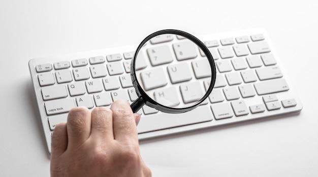 Schwarze lupe auf einer weißen tastatur auf weiß