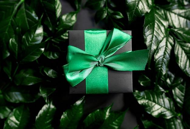 Schwarze luxusgeschenkbox mit grünem band auf dunklem hintergrund mit blättern an den seiten, flache lage, naturkonzept.