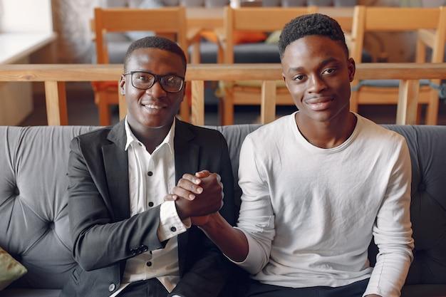 Schwarze männer in einem café, das ein geschäft hat