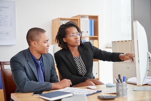 Schwarze männliche und weibliche kollegen, die im büro sitzen und zusammen bildschirm betrachten