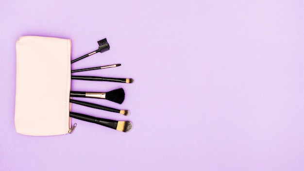 Schwarze make-upbürsten in der beige tasche auf purpurrotem hintergrund