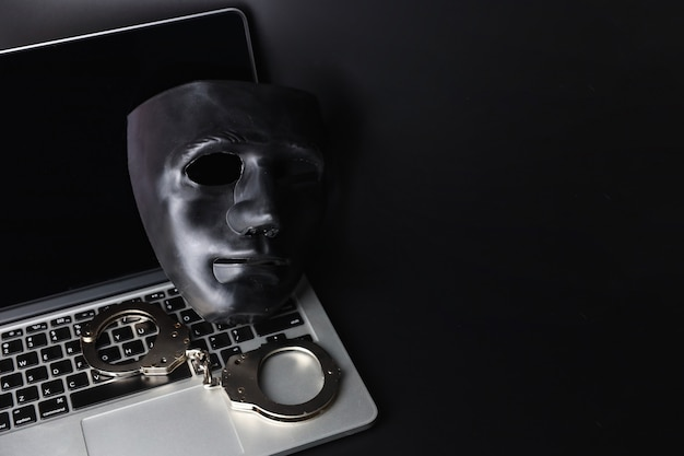 Schwarze maske und handschellen am computer auf schwarz