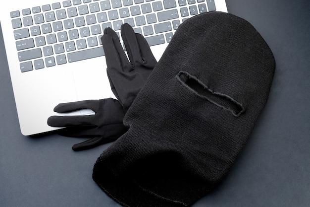 Schwarze maske und schwarze handschuhe auf einem laptop
