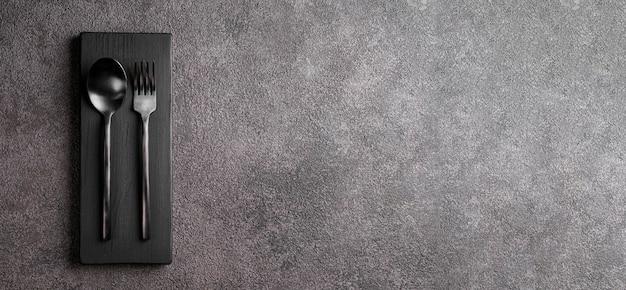 Schwarze matte gabel und löffel. grauer hintergrund des kopierraumkonzepts für ein restaurantmenü oder eine einladung zu einer feier. stilvoller minimalismus.