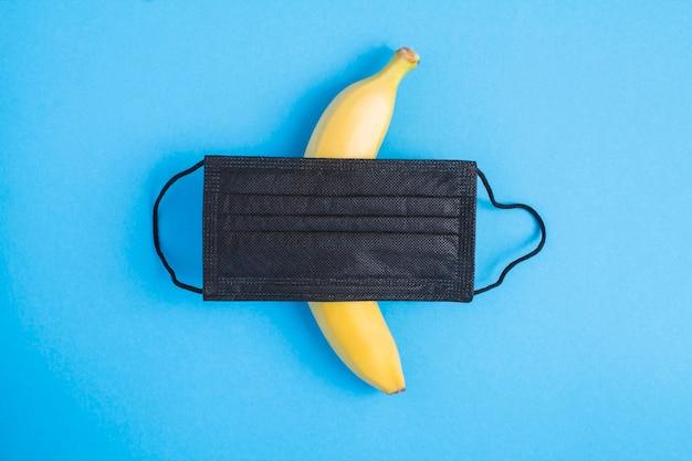 Schwarze medizinische maske und banane in der mitte des blaus