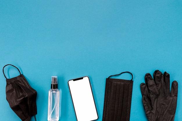 Schwarze medizinische maske und handschuhe der draufsicht mit leerem telefon