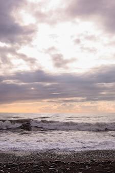 Schwarze meereswellen und bewölkter himmel