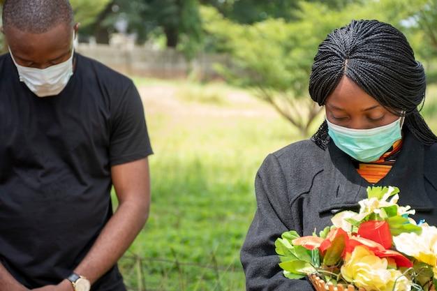 Schwarze menschen, die durch coronavirus verlorene menschen trauern, gesichtsmasken tragen, physische distanzierung
