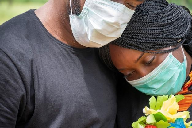 Schwarze menschen, die um coronavirus trauern, gesichtsmasken tragen, sich gegenseitig unterstützen, sich umarmen