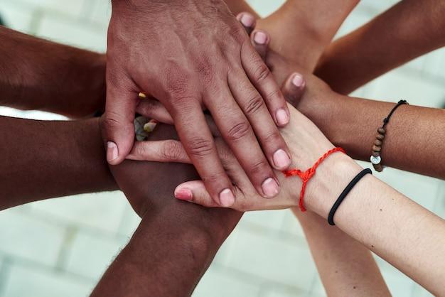 Schwarze menschen mit händen schlossen sich an. gruppe von menschen, die hände zusammen stapeln.