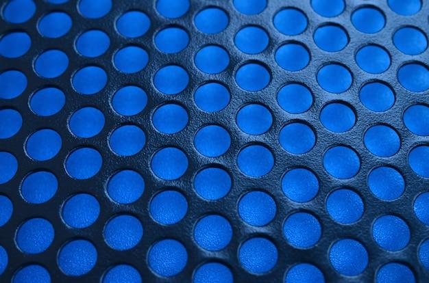 Schwarze metallcomputergehäusetafelmasche mit löchern auf blauem hintergrund. nahes hohes bild der zusammenfassung