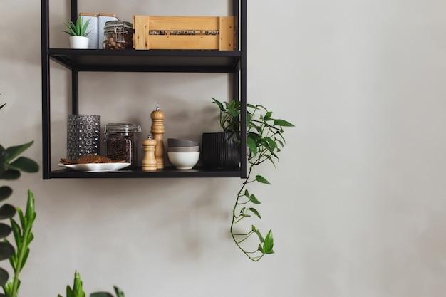 Schwarze metallregale in der küche auf einer grauen betonwand im loftstil. grüne blumentöpfe.