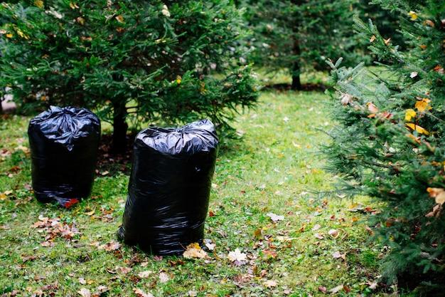 Schwarze müllsäcke gefüllt mit abgefallenen blättern